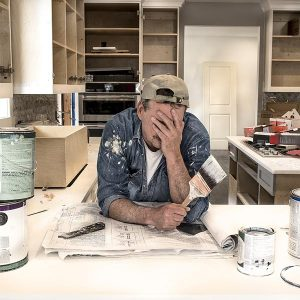 A stressed guy trying to paint his cabinet